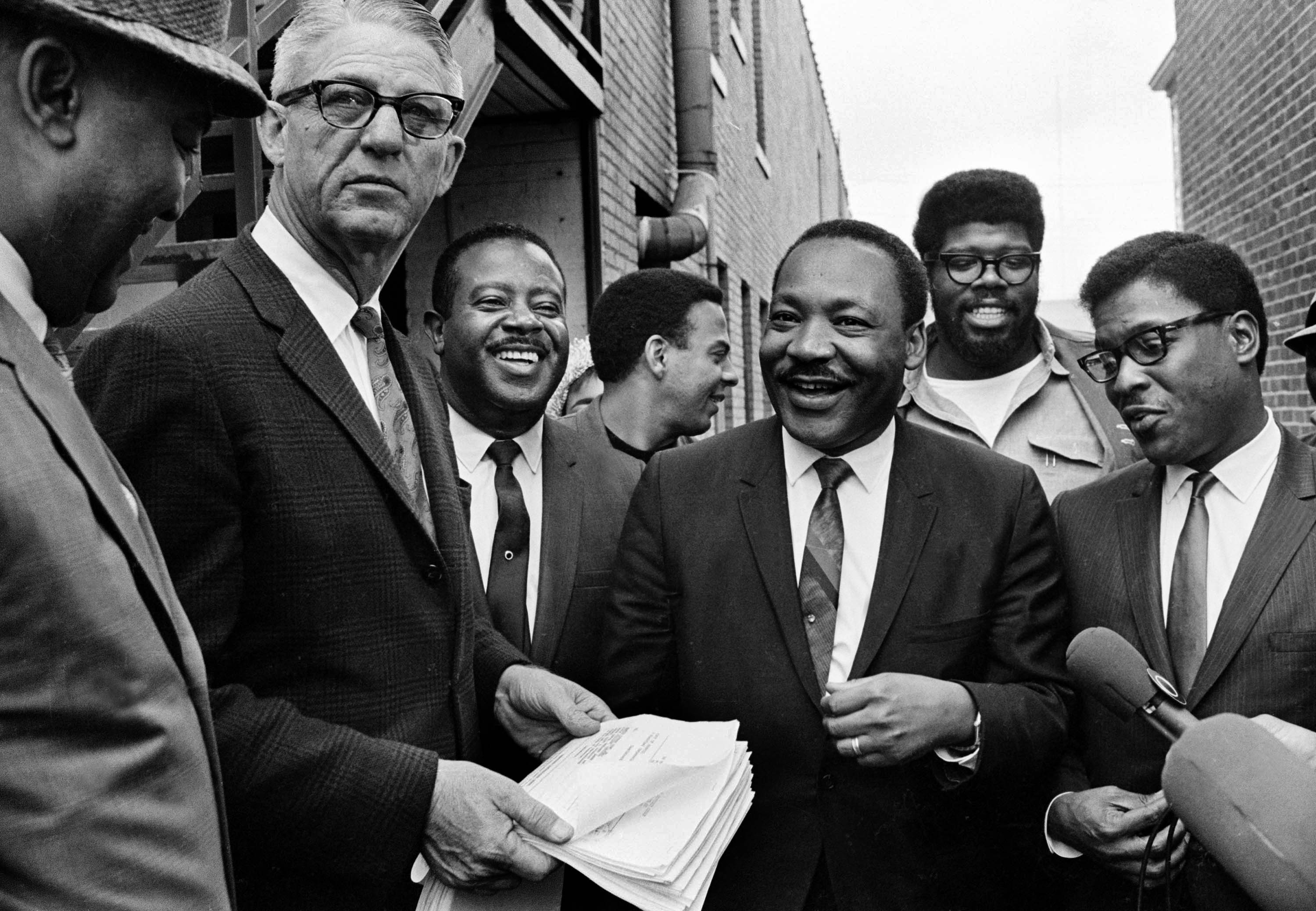 Dr. Martin Luther King Jr., center, and Rev. Ralph Abernathy, third from left, share a laugh outside court in Atlanta, Ga., Oct. 25, 1960.