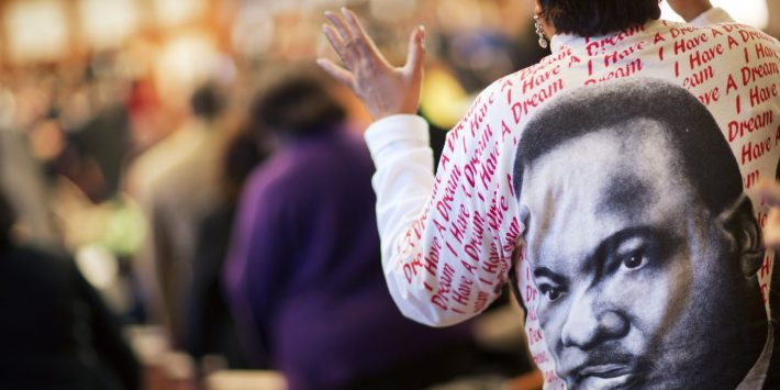 Gail Hollin wears a shirt bearing the image of the Rev. Martin Luther King Jr. as she sings during the King holiday commemorative service at Ebenezer Baptist Church where he preached, Monday, Jan. 18, 2016, in Atlanta.