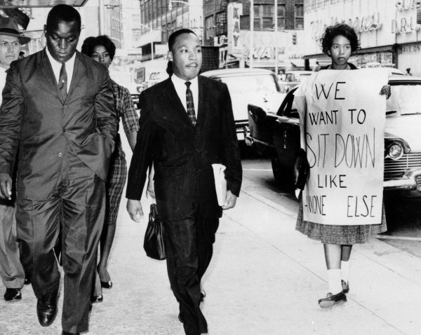 Dr. Martin Luther King Jr. under arrest by Atlanta Police Captain R.E. Little, left rear, passes through a picket line in front of a downtown department store on Oct. 9, 1960. with King is another demonstration leader, Lonnie King and an unidentified woman. The integration leader was among the 48 African-Americans arrested following demonstrations at several department and variety stores protesting lunch counter segregation. (AP Photo/stf)