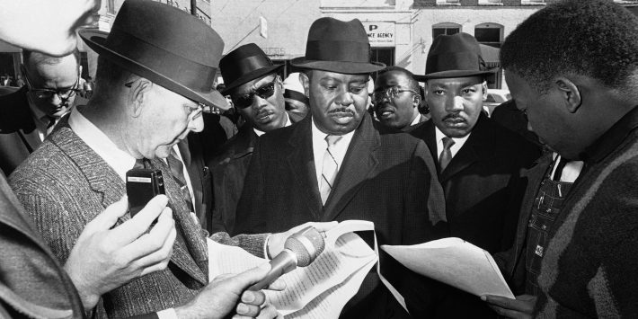 Chief Deputy U.S. Marshal H. Stanley Fountain, left, reads court order to Dr. Martin Luther King, right, and Ralph Abernathy, center, as they arrive at court house in Selma, Alabama on Jan. 25, 1965, to urge African Americans to register to vote.